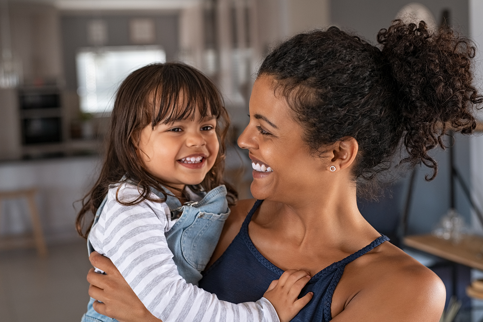 Mom holding daughter and smiling. If you're struggling to be present due to work, relationships or other tasks, get support with therapy for moms in Detroit, MI. No longer be an overwhelmed mom with the help of an online therapist. Additionally we provide therapy for new moms as well.