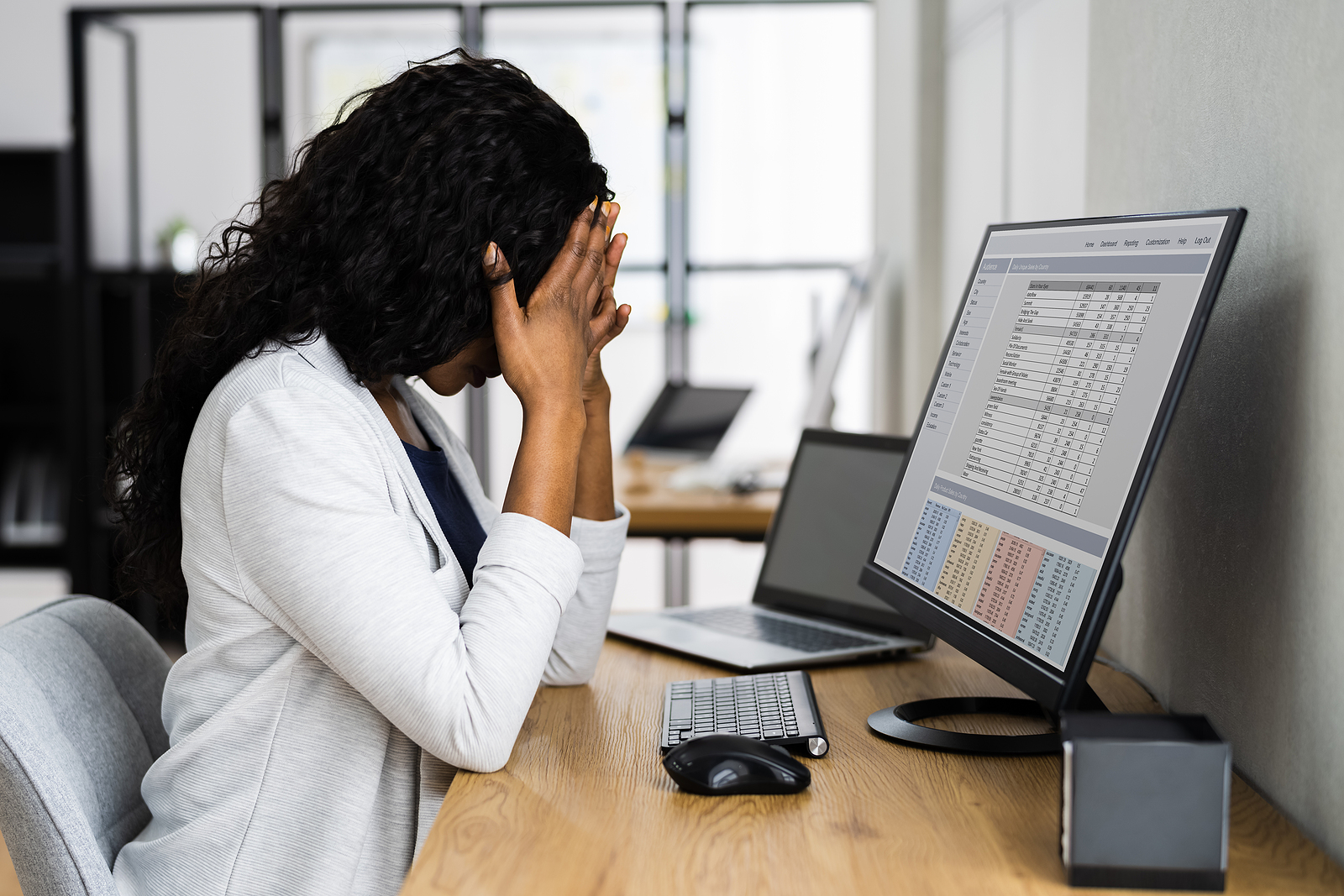 Woman sitting at desk stressed out. When you're a mom you have a lot on your plate. Get the support you need in therapy for moms in Detroit, MI today. Move past being an overwhelmed mom and find peace.