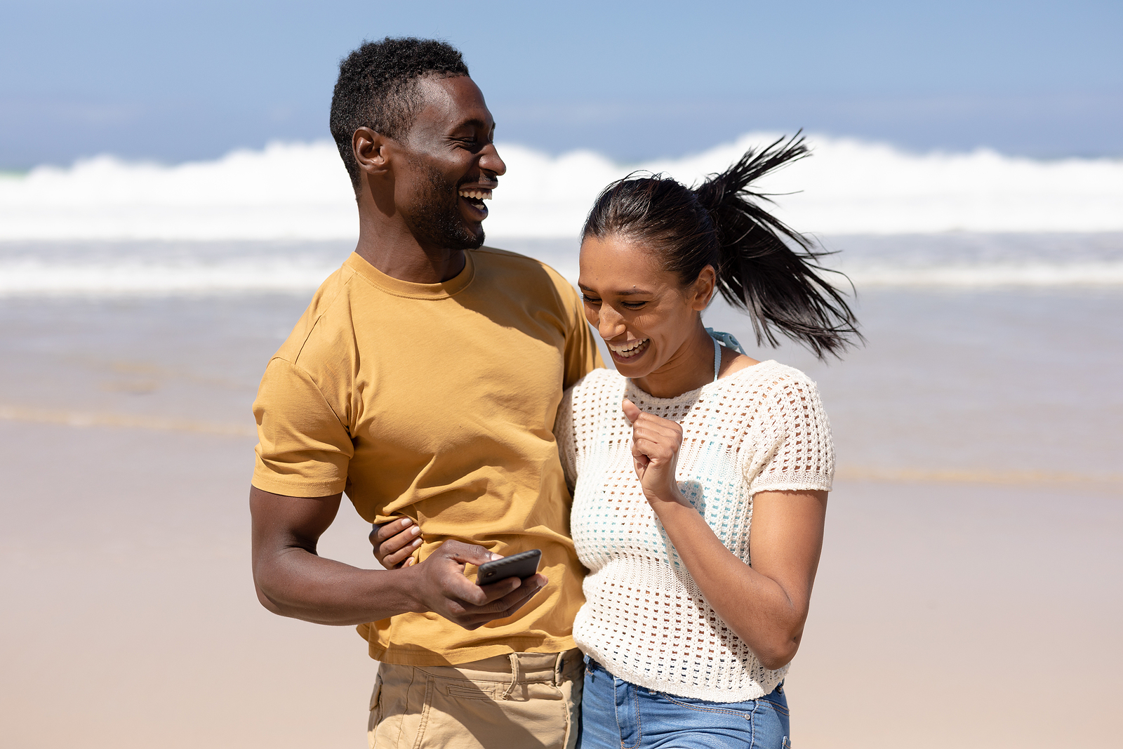 Happy interracial couple holding each other and smiling at the beach. Our therapists are here to guide you toward better mental heath. Get the support you have been seeking in online therapy in Michigan today. We provide therapy for anxiety, trauma, perfectionism, couples, working professionals, and more. Call now!