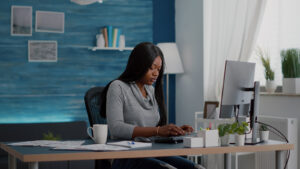 Woman in office on laptop at desk blue wall in background. Get your counseling FAQ's answered here. Our therapists offer insurance rates and private pay. Call now and begin online therapy in detroit, mi with our skilled black therapists.