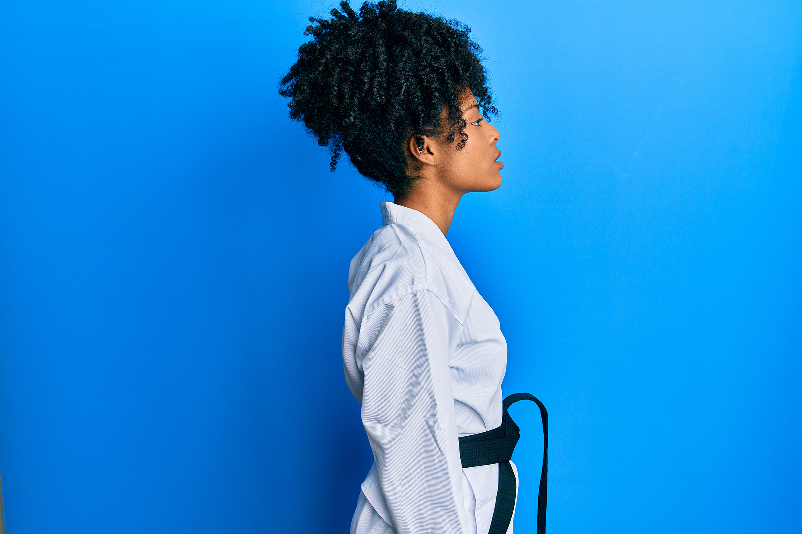 Woman in karate outfit standing to the side of blue background. Dealing with life transitions, anxiety, trauma, and more is hard. Get support in Acceptance and Commitment Therapy in detroit, mI. With principles from the act hexaflex model, we can help you. Call now to begin act therapy!