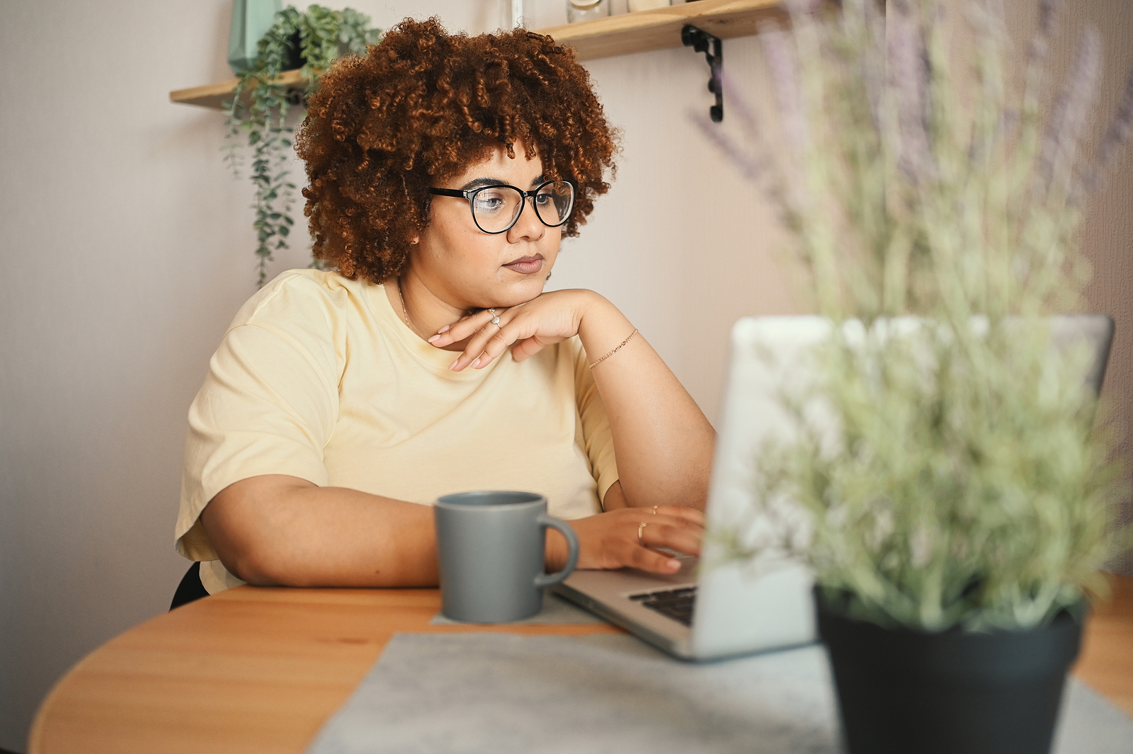 Black woman on laptop, plants in foreground and background. If you're wondering with online therapy in Michigan or therapy in Detroit, MI is for you then get in touch. You will work with one of our talented black woman therapists near you or online. Call now!