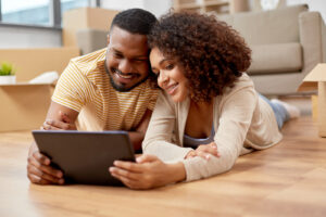 Black couple laying on floor with both holding tablet. Are you wanting to begin therapy in Detroit, MI? Then learn about our insurance policies, cancellations, and more. Begin online therapy in Detroit, MI or Michigan and get support from one of our skilled black therapists!