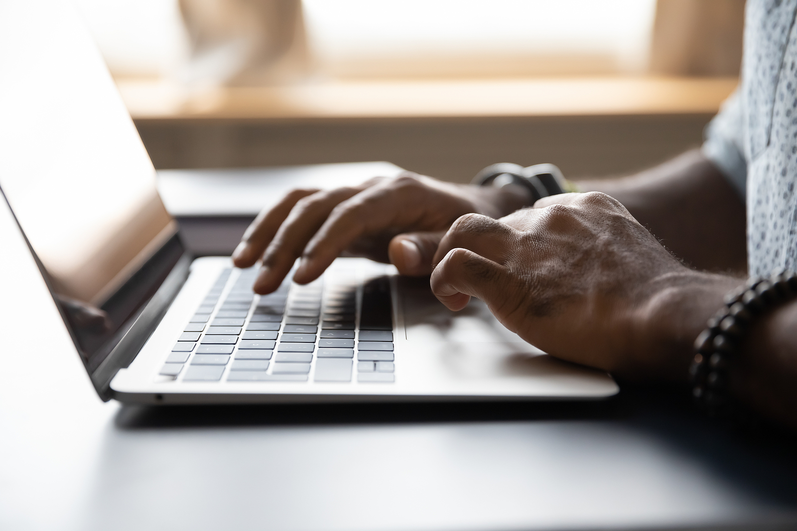 Close up African American male hands typing on laptop keyboard. If you're ready for support, online therapy in Michigan is for you. We can help you with anxiety, trauma, perfectionists, grief, and more. Begin therapy in Detroit, MI when you're ready!